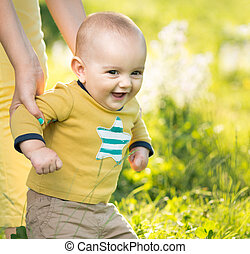 boy walking on the grass by  parent