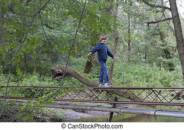 Boy walking over a bridge in the forest