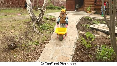 Boy walking with barrow wheel trolley in garden - Baby boy...