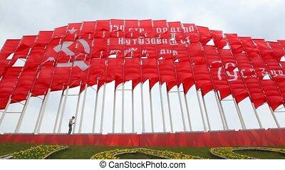 boy walks against huge communist red flags