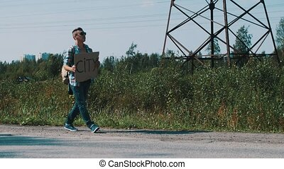 Boy walks along road hold cardboard plate with sign city....