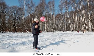 boy walks and plays with a balloon with propeller in winter...