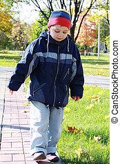 Boy walks in park