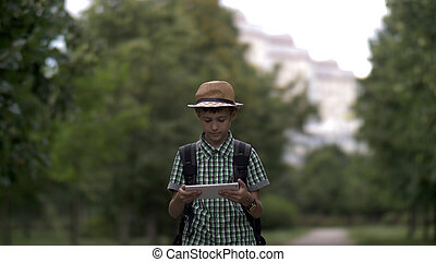 boy walks in the park and uses a tablet