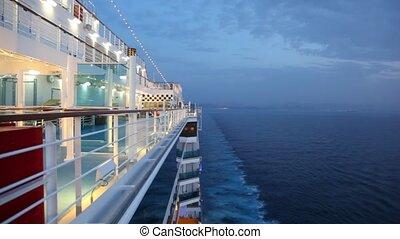 boy walks on cruise ship in night sea