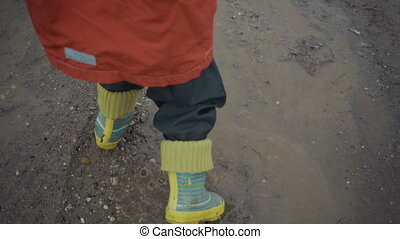 boy walks through the puddles and mud in the spring. - boy...