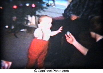 A cute baby boy with red suspenders tries to walk towards a shiny Christmas decoration. (Scan from archival 8mm film)