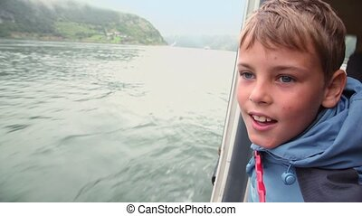 Boy watch from rescue boat which floats on fjord with...