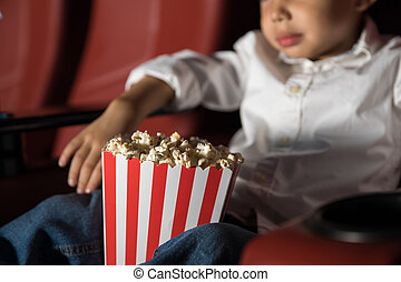 Boy watching movie and eating popcorn