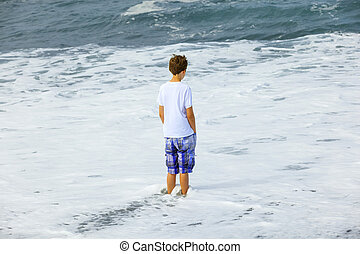 boy watching the waves of the ocean