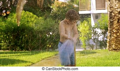 Boy watering the lawn and getting wet