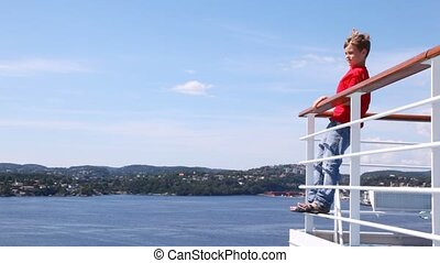 Boy waves greeting by hand standing on ship handrail