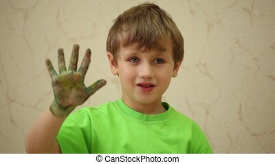 Boy waves his right palm smeared with coloured paints
