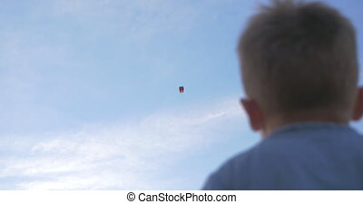 Boy Waving to Sky Lantern - Low-angle shot of a boy waving...
