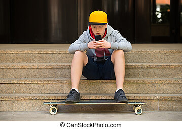 Boy Wearing Cap Looking At Cellphone