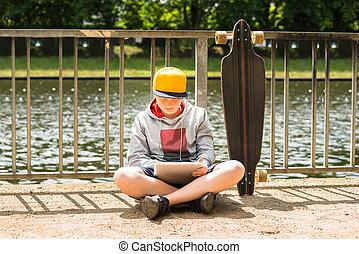 Boy Wearing Cap Using Digital Tablet