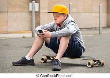 Boy Wearing Cap Using Smartphone