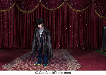 Boy Wearing Clown Make Up and Large Coat on Stage