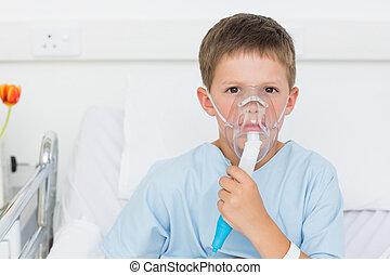 Boy wearing oxygen mask in hospital bed - Portrait of sick...