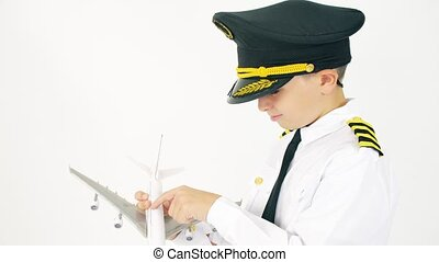 Boy wearing pilot's uniform examines airliner scale model -...