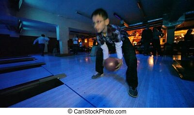 Boy wearing spectacles throws ball in bowling club, the rear...