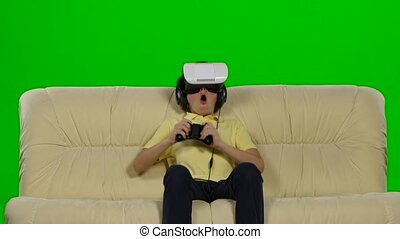 Boy wearing virtual reality goggles. Studio shot, white couch. Green screeen
