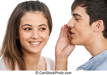 Boy whispering in cute girls ear.