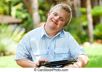 Close up portrait of handicapped boy playing on digital tablet outdoors.