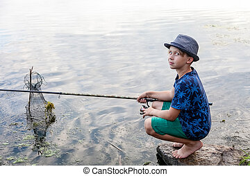 Boy with a fishing rod catches a fish