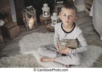Boy with a gift squatting on rug at home