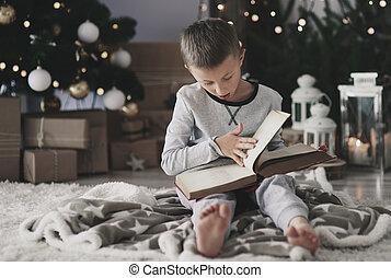 Boy with a magic book on floor