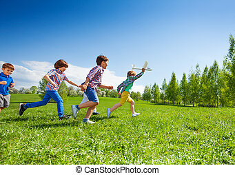 Boy with airplane and following him children run