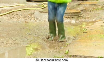 boy with an umbrella jumping in a puddle - The boy is...