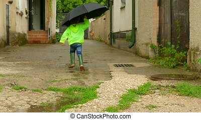 boy with an umbrella running around the yard in rubber boots...