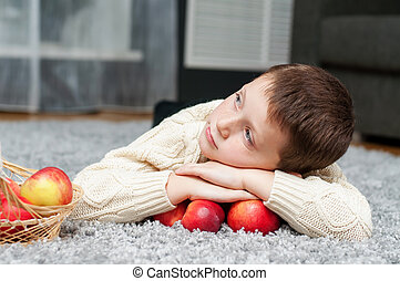 Boy with apples lies on the carpet