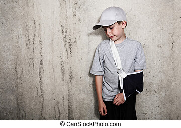 Boy with arm in a sling from a broken humerus wearing a baseball cap