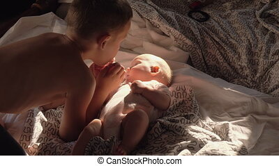Boy with baby at home. He loves little sister and kissing her on the cheek