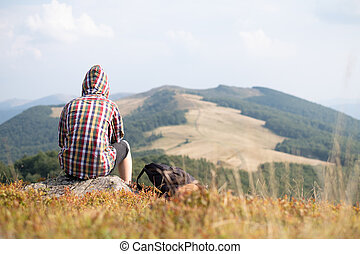 Boy with backpack in autumn mountains