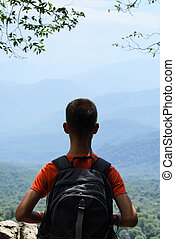 Boy with backpack on mountains background