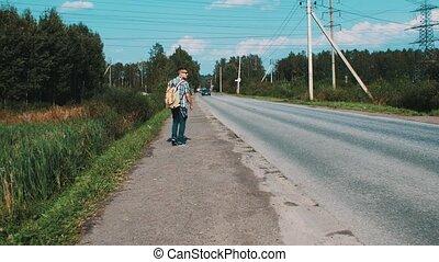 Boy with backpack walking along roadside. Hitchhiking....