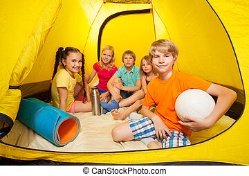 Boy with ball and friends in camping tent
