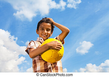 Boy with ball over sky