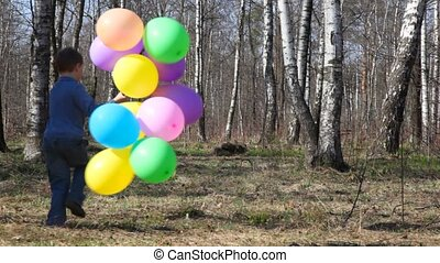 boy with balloons runs to spring forest