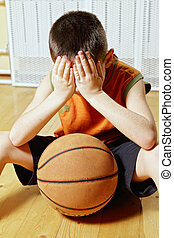 Boy with basketball on floor closeup