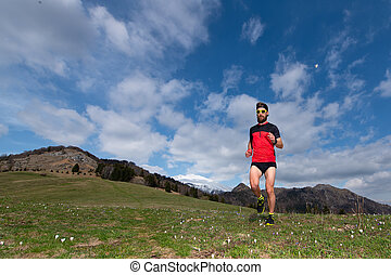 Boy with beard while running in a mountain meadow