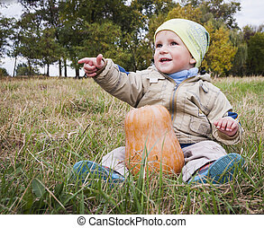boy with big yellow pumpkin in hands sitting on the grass