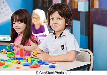 Boy With Blocks While Friends Playing In Background