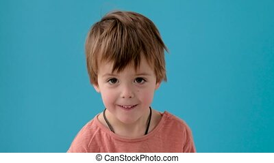 Adorable little boy with short blond hair in orange t-shirt nods head posing for camera against bright azure wall close view