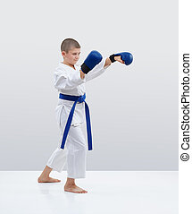 Boy with blue overlays on his hands strikes a blow