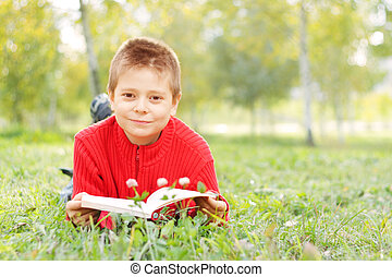Boy with book laying on grass